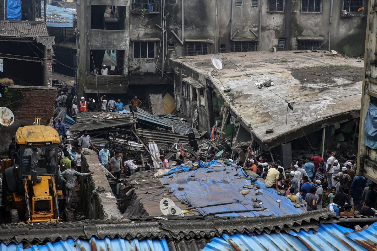 People gather at the scene of a residential building's collapse in Bhiwandi on Sept 21, 2020.