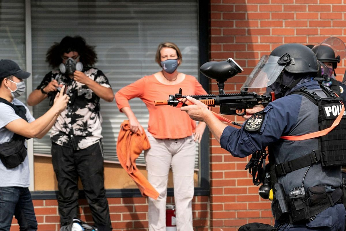 Louisville Police fire a pepper ball gun into a crowd during a protest after a decision in the case against police officers involved in the death of Breonna Taylor, who was shot dead by police in her apartment, in Louisville, Kentucky, U.S. September