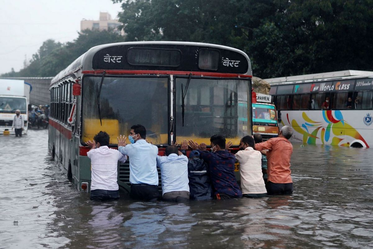 People push a bus through a waterlogged road after heavy rainfall in Mumbai, India, September 23, 2020. PHOTO: REUTERS