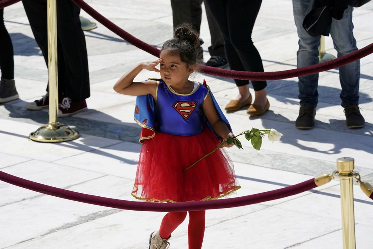 A child in a Supergirl costume pays respects as Justice Ruth Bader Ginsburg lies in repose under the Portico at the top of the front steps of the U.S. Supreme Court building, in Washington, U.S. September 23, 2020. PHOTO: POOL VIA REUTERS