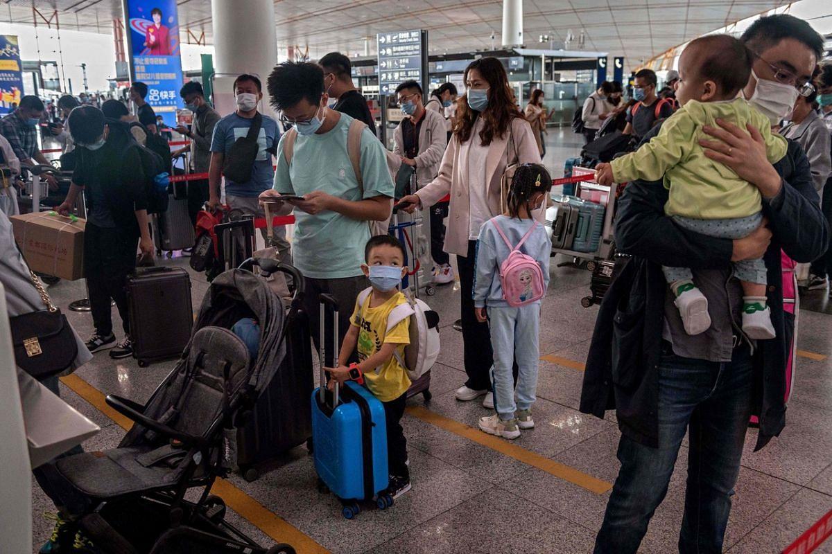 """People queue up to check in for domestic flights ahead of the country's national """"Golden Week"""" holiday at Beijing's Capital International Airport, on Sept 30, 2020."""