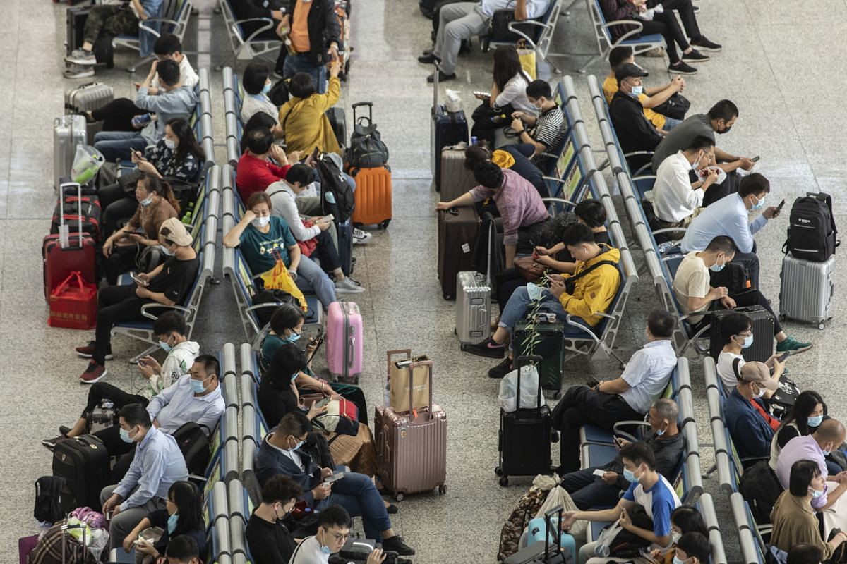 Passengers wait in the departure hall of Hongqiao High-speed Railway Station in Shanghai, China, on Sept 30, 2020.