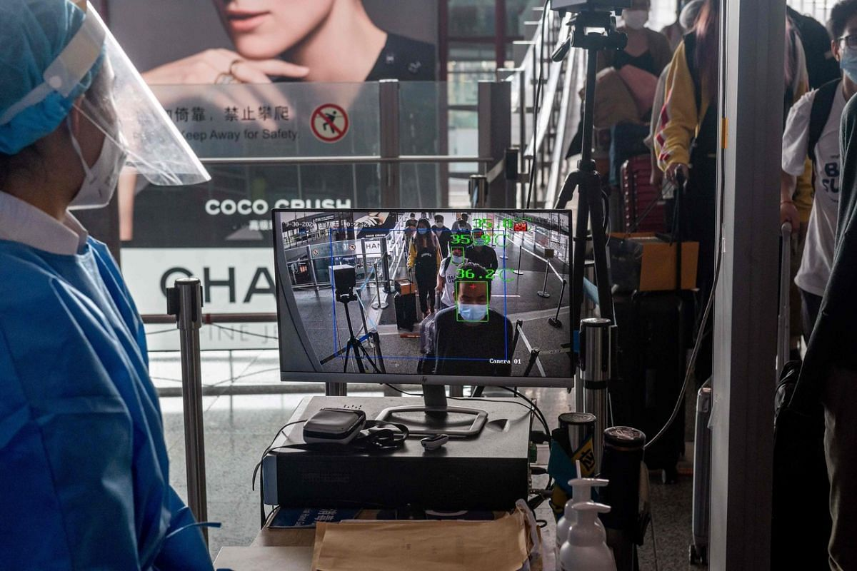 """A worker wearing full protective gear watches a monitor that reads passengers temperatures at a security checkpoint ahead of the country's national """"Golden Week"""" holiday at Beijing's Capital International Airport, on Sept 30, 2020."""