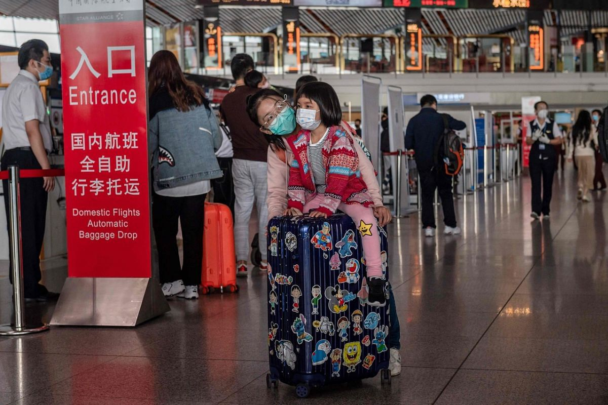 """A girl wearing a face mask sits on top of a bag as she travels with relatives ahead of the country's national """"Golden Week"""" holiday at Beijing's Capital International Airport, on Sept 30, 2020."""