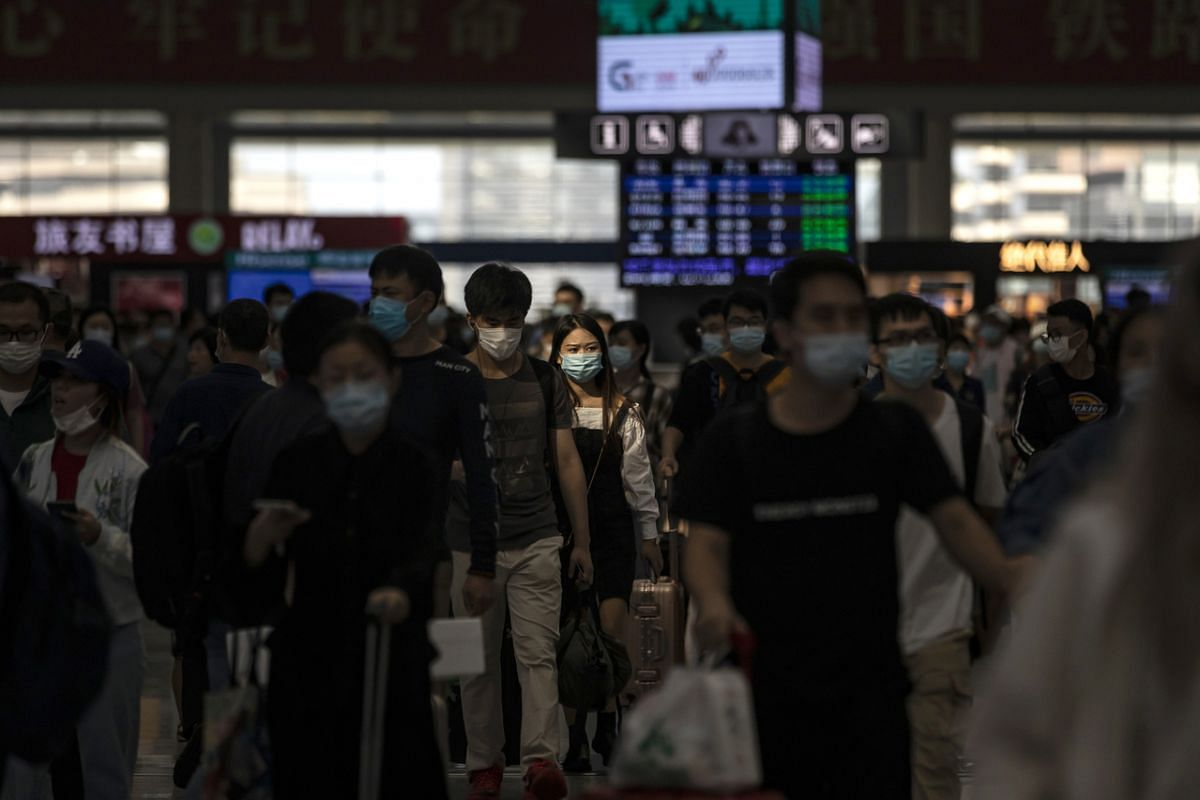 Passengers wearing protective masks carry their luggage through the main hall of the departure hall of Hongqiao High-speed Railway Station in Shanghai, China, on Sept 30, 2020.