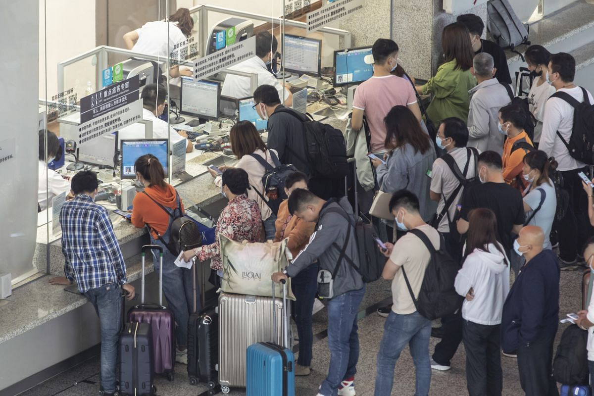 Passengers wearing protective masks stand in line at ticket counters in the departure hall of Hongqiao High-speed Railway Station in Shanghai, China, on Sept 30, 2020.
