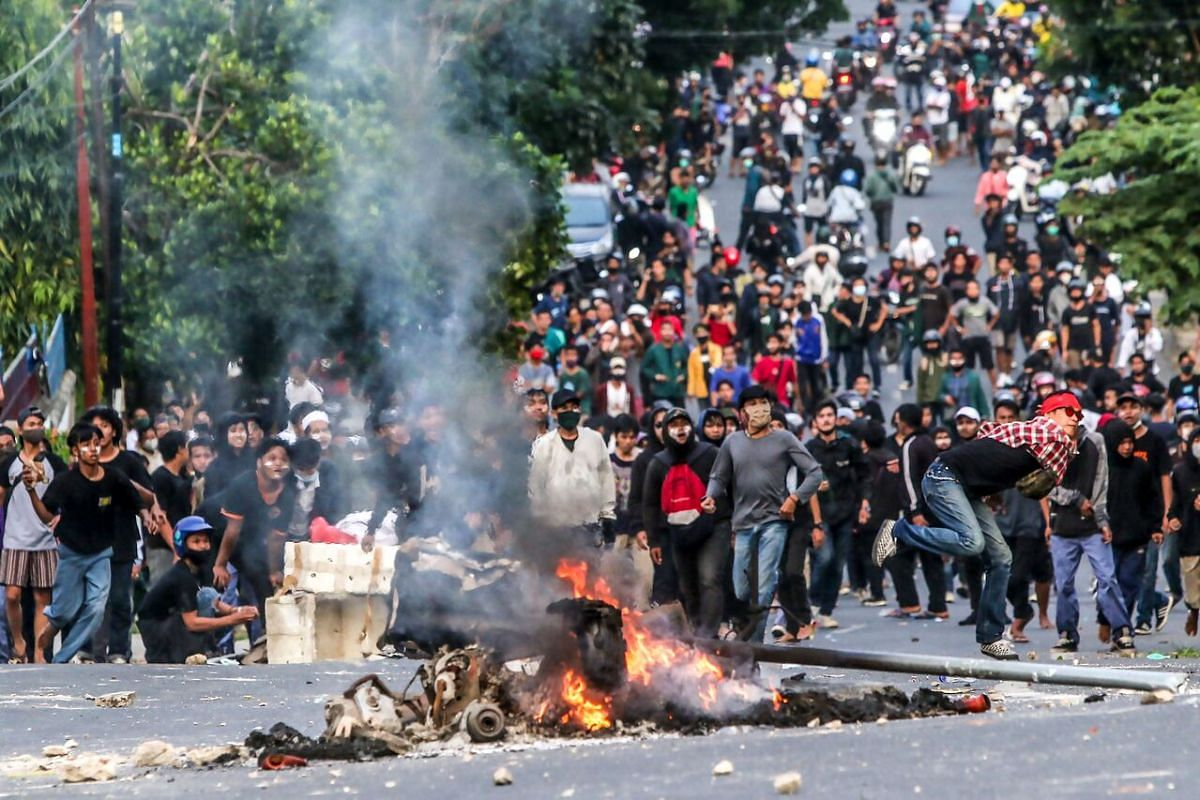 Youths throw stones at riot police during the second day of a three-day-strike in Lampung, Indonesia, on Oct 7, 2020.