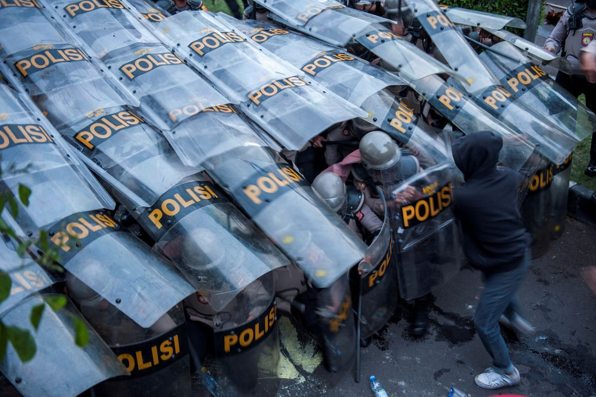 A demonstrator clashes with a barricade of police officers during a protest against the Indonesian government's proposed labour reforms outside the Regional Parliament building in Bandung, West Java, on Oct 6, 2020.