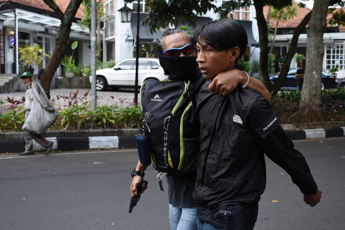 A plain-clothes police officer (left, wielding a gun) detains a youth during the second day of a three-day-strike by workers against a government bill on job creation, in Bandung, Indonesia, on Oct 7, 2020.