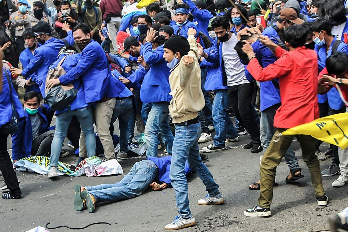 A person lies on the ground as students react after clashing with riot police during the second day of protests in Bekasi, Indonesia, on Oct 7, 2020.