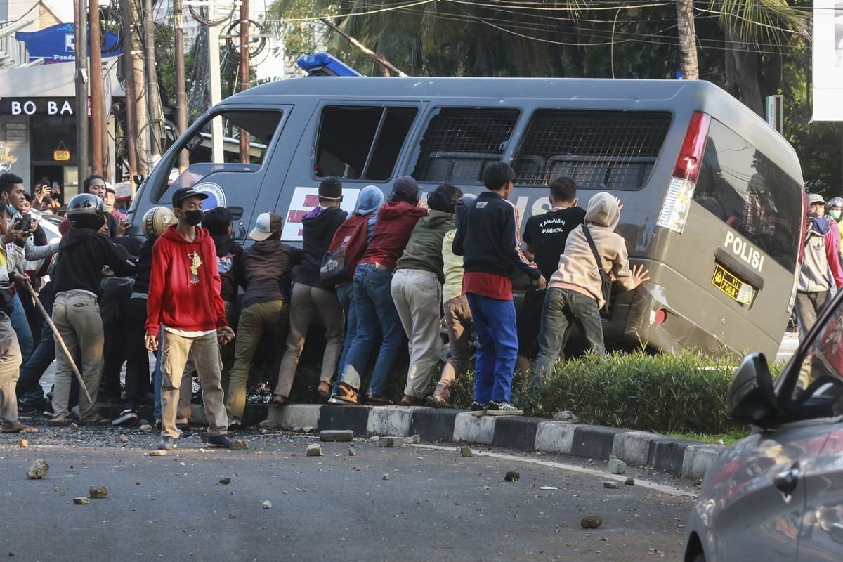 Students attempt to overturn a police vehicle during a protest in Jakarta, on Oct 7, 2020.