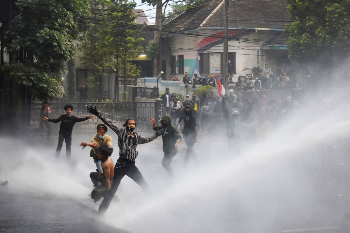 Riot police unleash water cannons to disperse student protesters during the second day of a three-day-strike in Bandung on Oct 7, 2020.