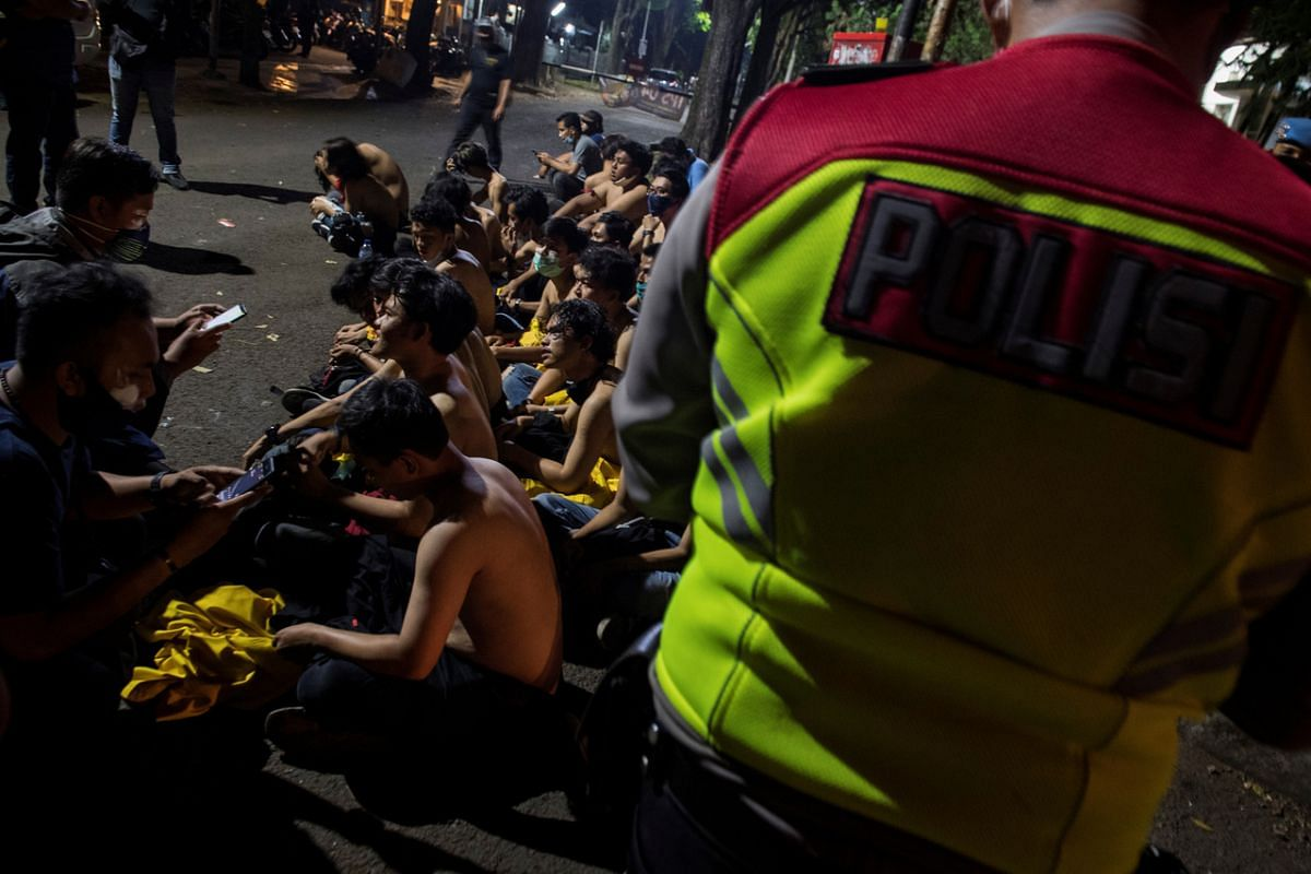 Demonstrators are detained during a protest in Banding, West Java, on Oct 7, 2020.
