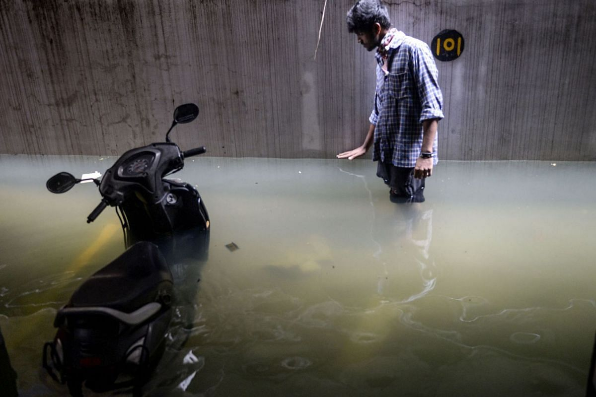 A resident shows the level of water in his cellar area at an apartment following heavy rains in Hyderabad, India, on October 14, 2020.
