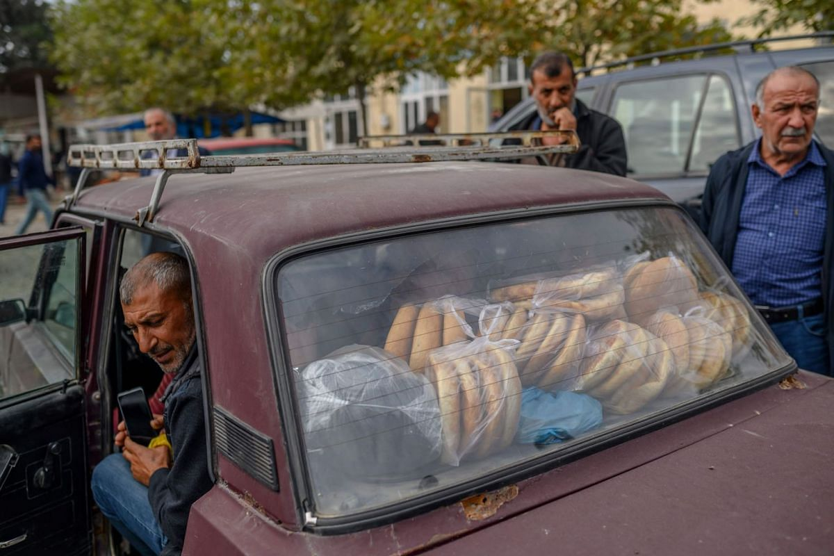 A man sits in a car full of bread to distribute to other people near Agdam city during the ongoing fighting between Armenia and Azerbaijan over the disputed region, in the city of Terter on October 14, 2020.