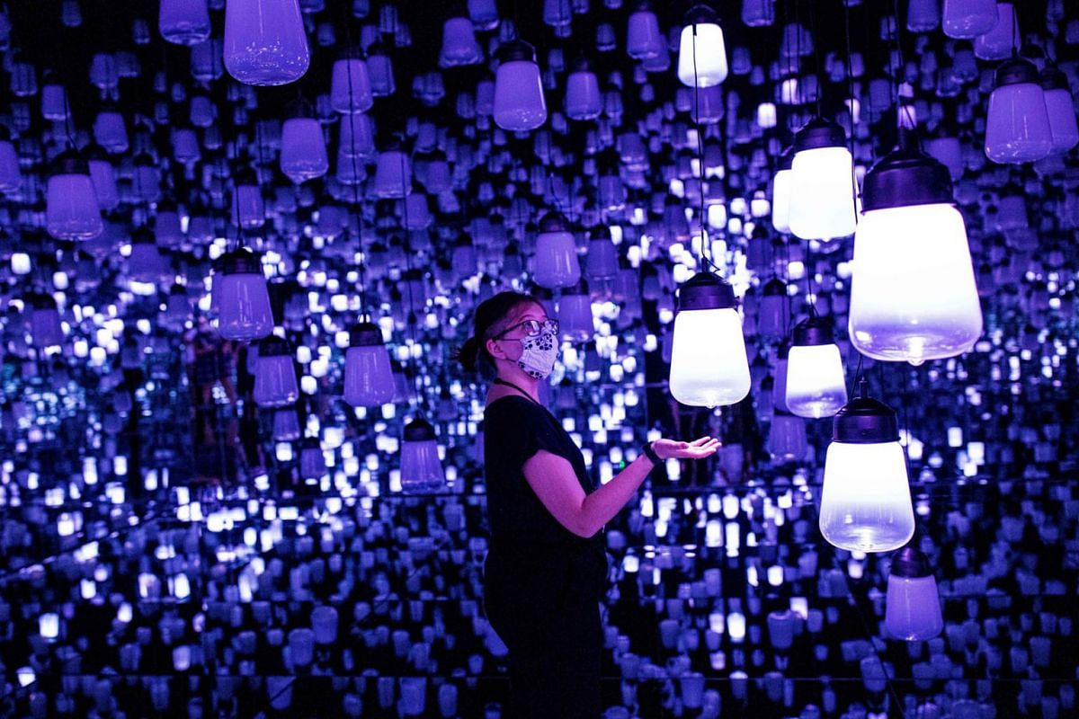 "In this photo taken on October 14, 2020, a member of Teamlab poses at the ""Forest of Lamps"" digital installation room with hanging lamps which illuminate as a visitor nears them, in the TeamLab Borderless exhibition at Mori Building Digital Art Museu"