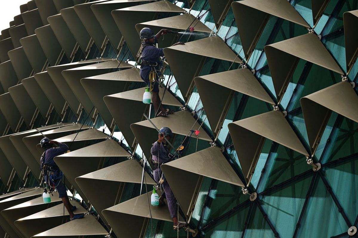 Workers cleaning the glass panels and sunshields on the roof of Esplanade – Theatres on the Bay on Oct 15, 2020.