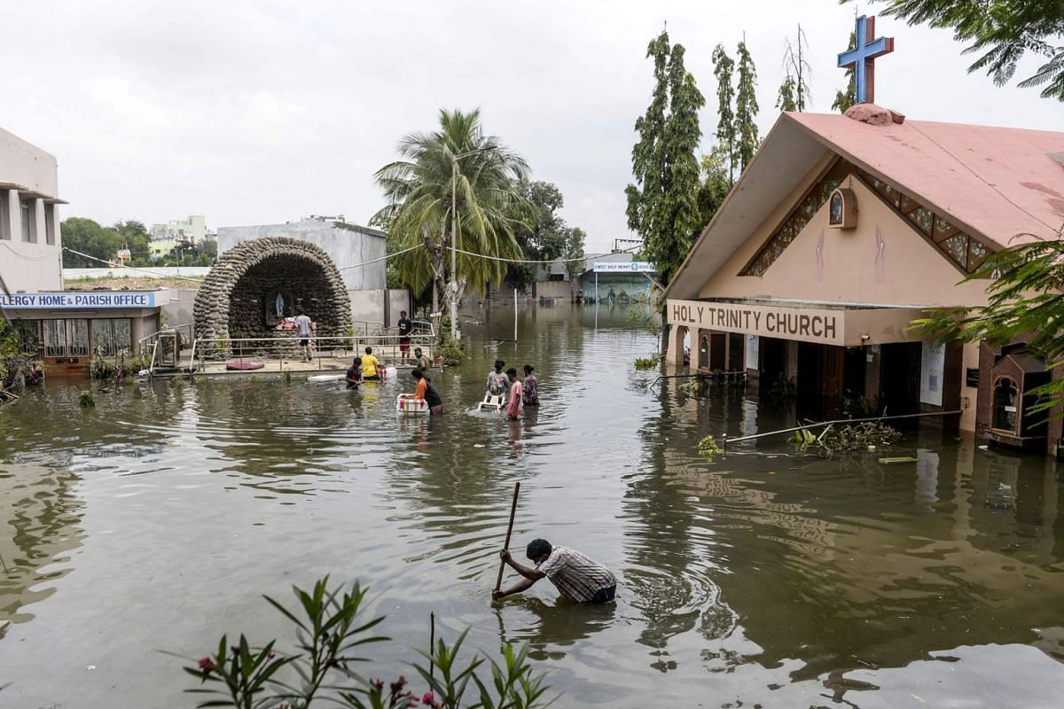 Parishioners carry material from the flooded Holy Trinity church following heavy rains in Hyderabad on October 15, 2020.