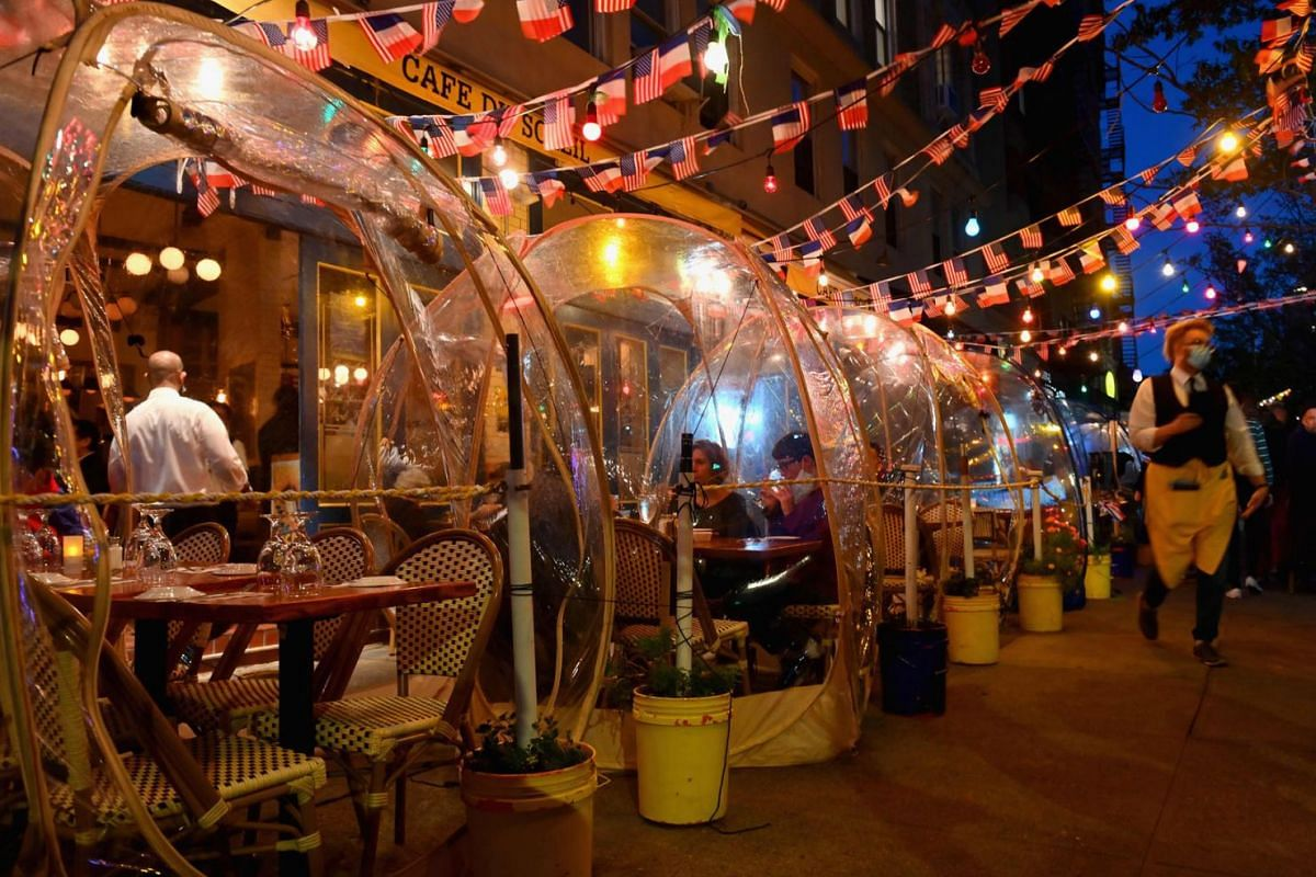 People dine in plastic tents for social distancing at a restaurant in Manhattan on October 15, 2020 in New York City, amid the coronavirus pandemic.