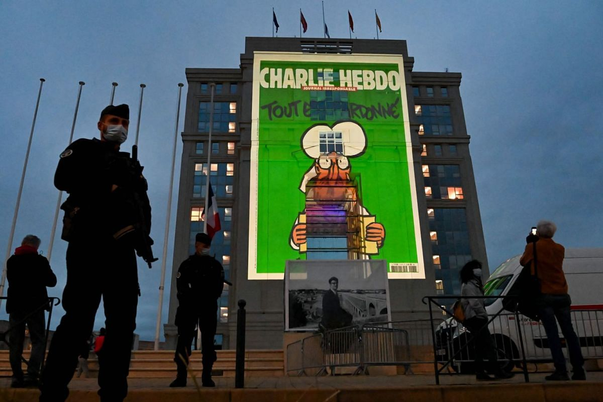 Police officers stand guard as cartoons of French satirical weekly newspaper Charlie Hebdo are projected onto the facade of the Hotel de Region in Montpellier, on October 21, 2020, during a national homage to French teacher Samuel Paty who was behead
