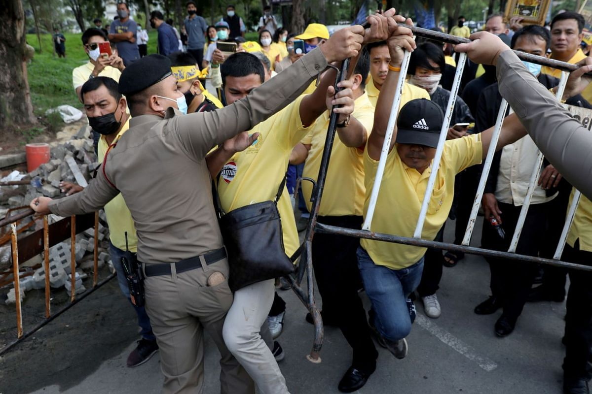 Police try to separate pro-democracy protesters and royalists (wearing yellow) during a clash in Bangkok, Thailand October 21, 2020.