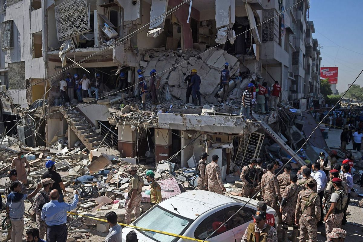 Security personnel and rescue workers are seen amid the debris of a multi-storey building that was damaged after an explosion in Pakistan's port city of Karachi on October 21, 2020.