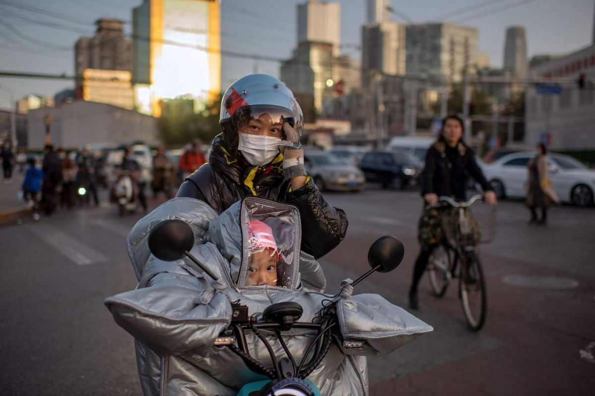A woman (C) wearing a face mask as a preventive measure against the Covid-19 coronavirus waits to cross a street with her daughter (C, down) as they both ride on an electric bike during rush hour in Beijing on October 21, 2020.