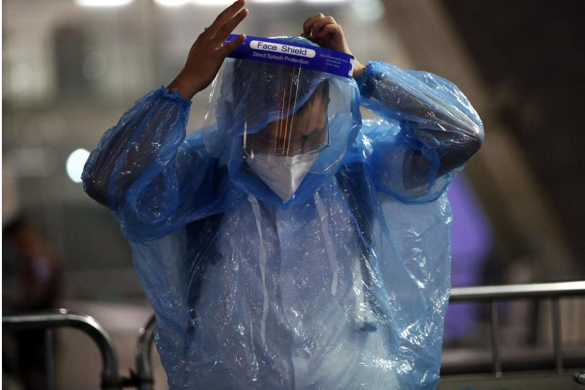 A Chinese tourist wearing raincoats and face shield as part of the Covid-19 coronavirus pandemic restrictions after arriving at Suvarnabhumi Airport in Thailand on Oct 20, 2020.