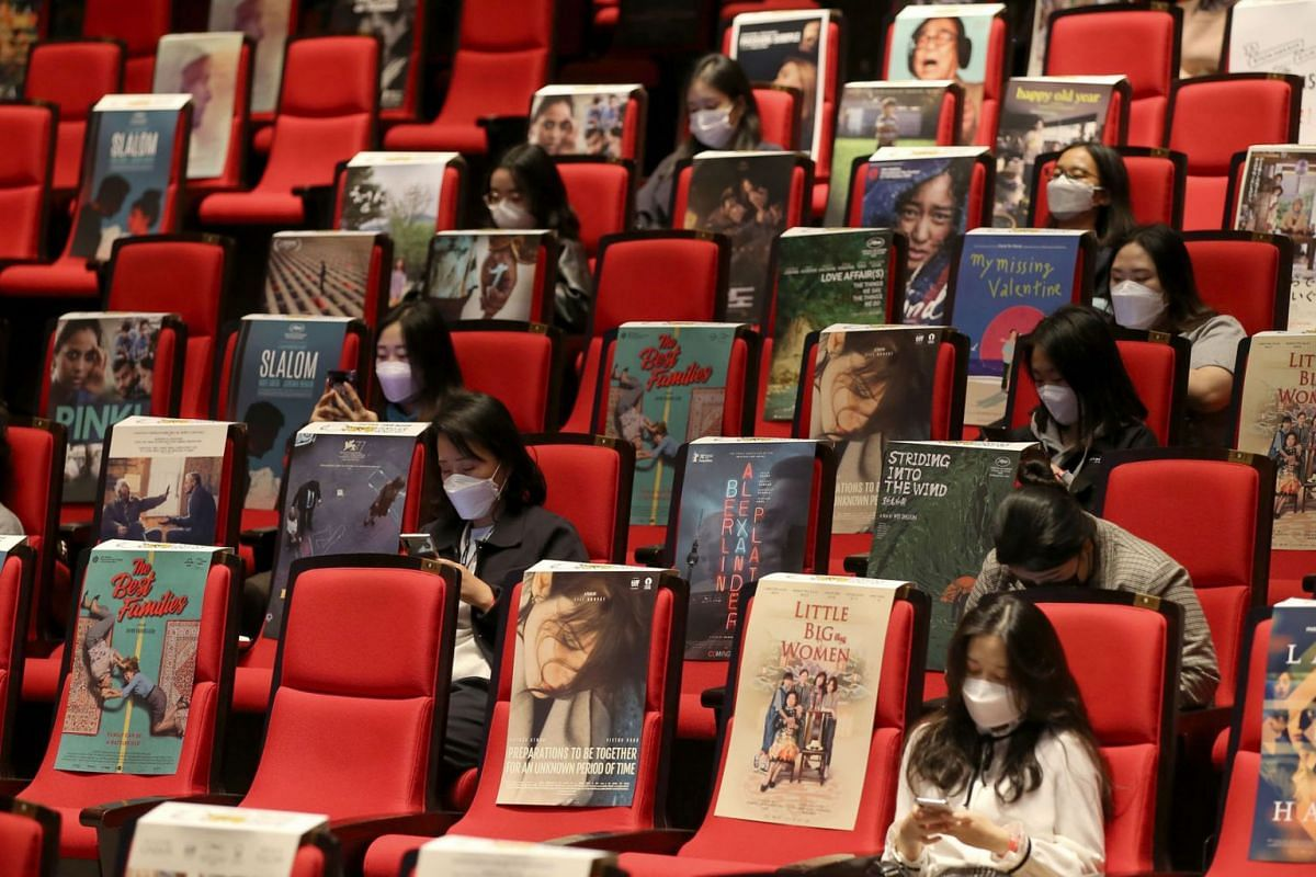 """This handout photo taken and released on October 21, 2020 by the Busan International Film Festival (BIFF) shows visitors sitting among movie posters to observe social distancing as they attend at a public talk about South Korean zombie thriller """"Peni"""