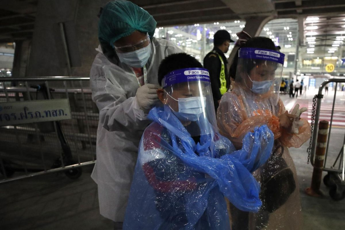 A Thai health official helps Chinese children wearing raincoats and face shields upon their arrival at Suvarnabhumi Airport on Oct 20, 2020.