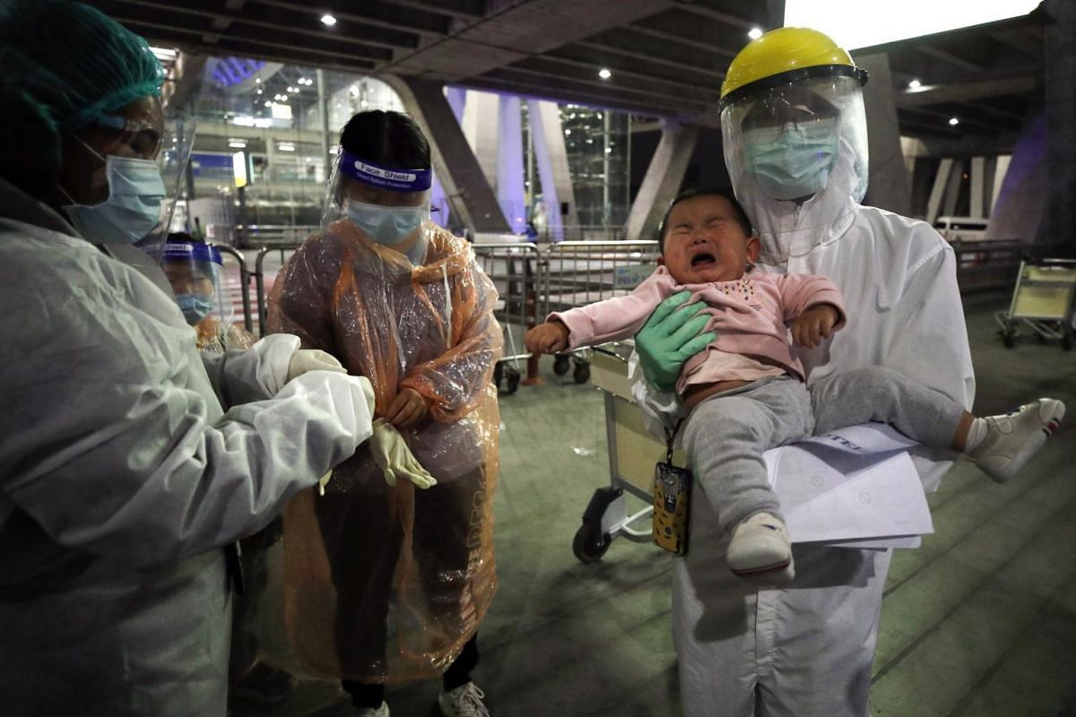 A Thai health official holds a Chinese baby as his mother put on a raincoat and face shield as part of the Covid-19 coronavirus pandemic restrictions.