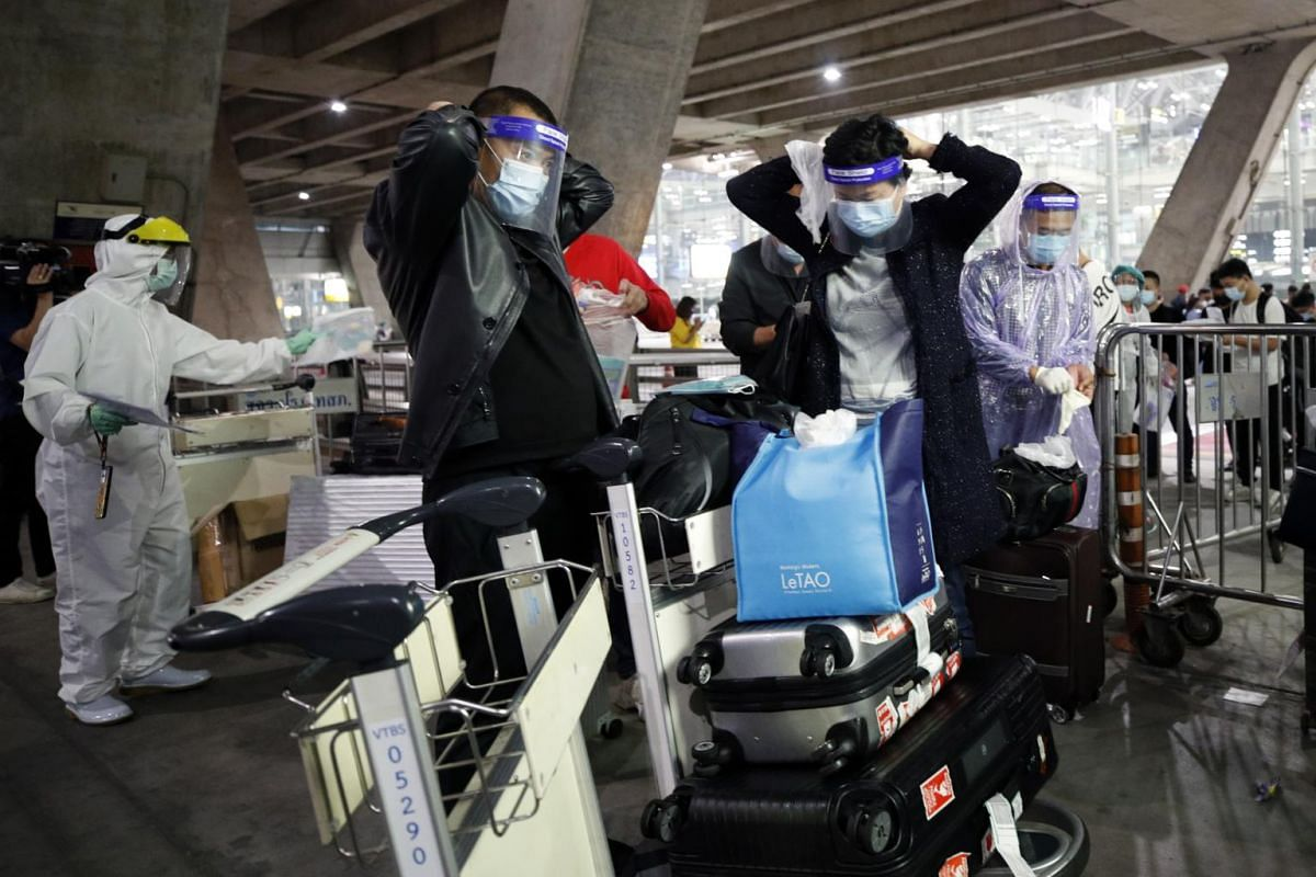 Chinese tourists put on raincoats and face shields as part of the Covid-19 coronavirus pandemic restrictions upon their arrival in Thailand on Oct 20, 2020.