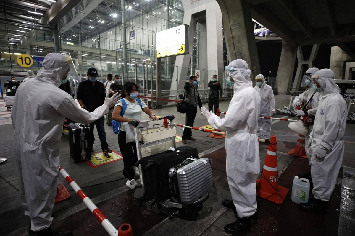 Thai health officials wearing protective suits disinfect belongings of Chinese tourists upon their arrival at Suvarnabhumi Airport in Thailand on Oct 20, 2020.