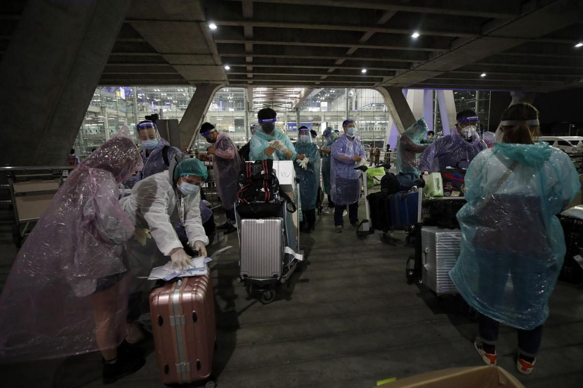 Chinese tourists wearing raincoats and face shields upon their arrival at Suvarnabhumi Airport in Thailand on Oct 20, 2020.