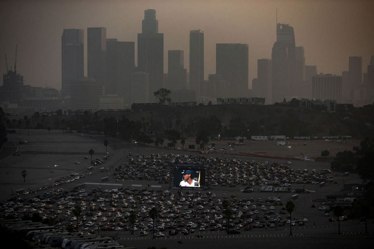 Los Angeles Dodgers' fans watch game two of the World Series 2020 between the Tampa Bay Rays and Los Angeles Dodgers, at a drive-in organized on the grounds of Dodger Stadium (foreground) amid the coronavirus pandemic in Los Angeles, California, USA,