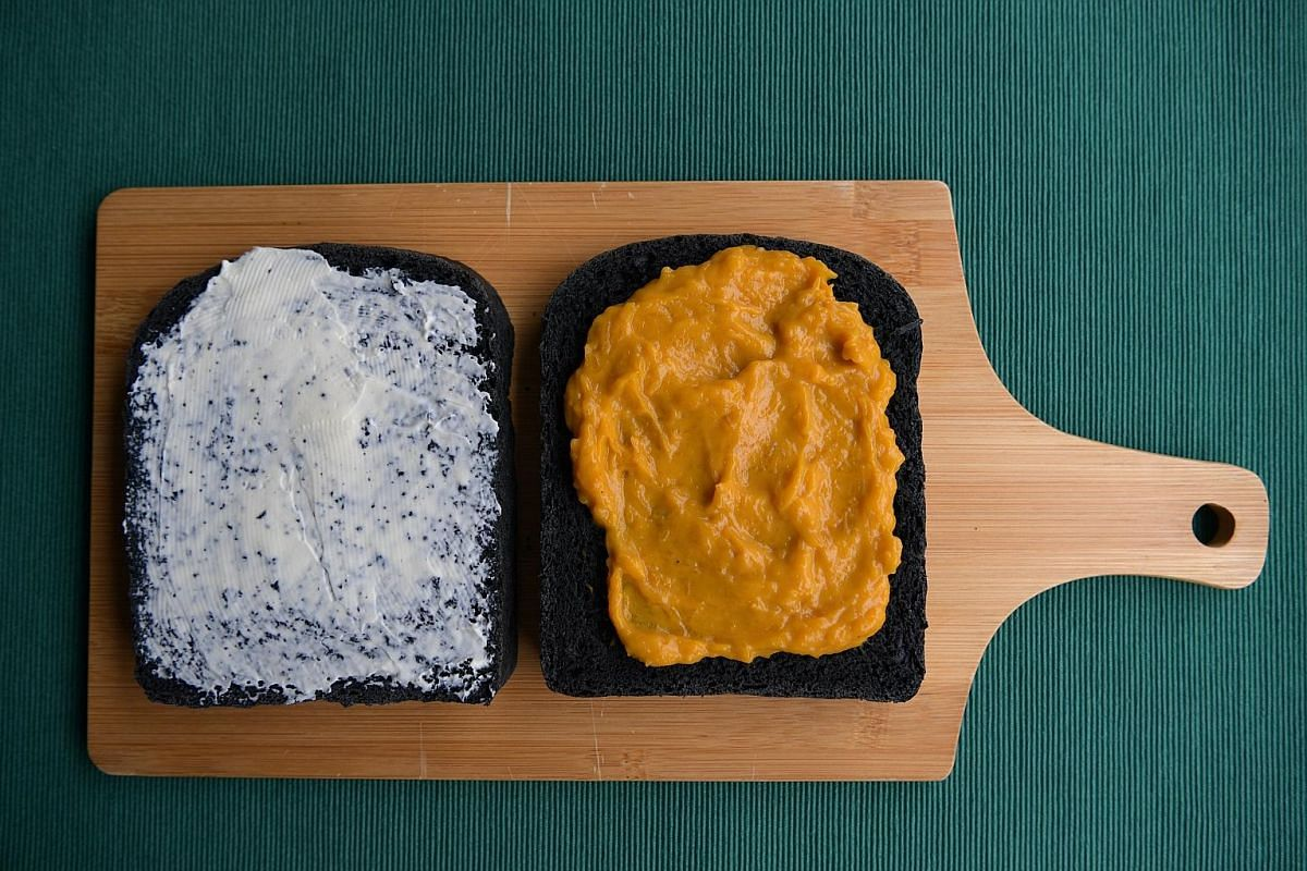 Slices of charcoal bread smeared with cream cheese (far left) and pumpkin spread (left). The dough used to make charcoal bread is versatile and quite easy to work with.