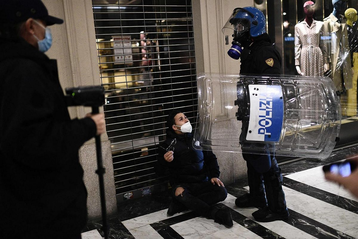 Italian police officers detain a far-right activist during a protest against the government restriction measures in downtown Turin, Italy, on Oct 26, 2020.