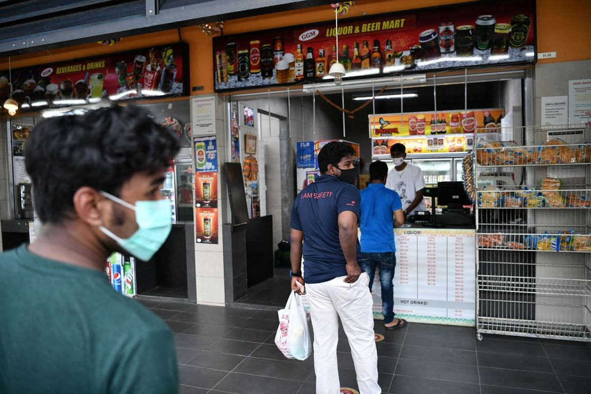 Foreign workers queuing to buy beverages at Tuas South Recreation Centre.
