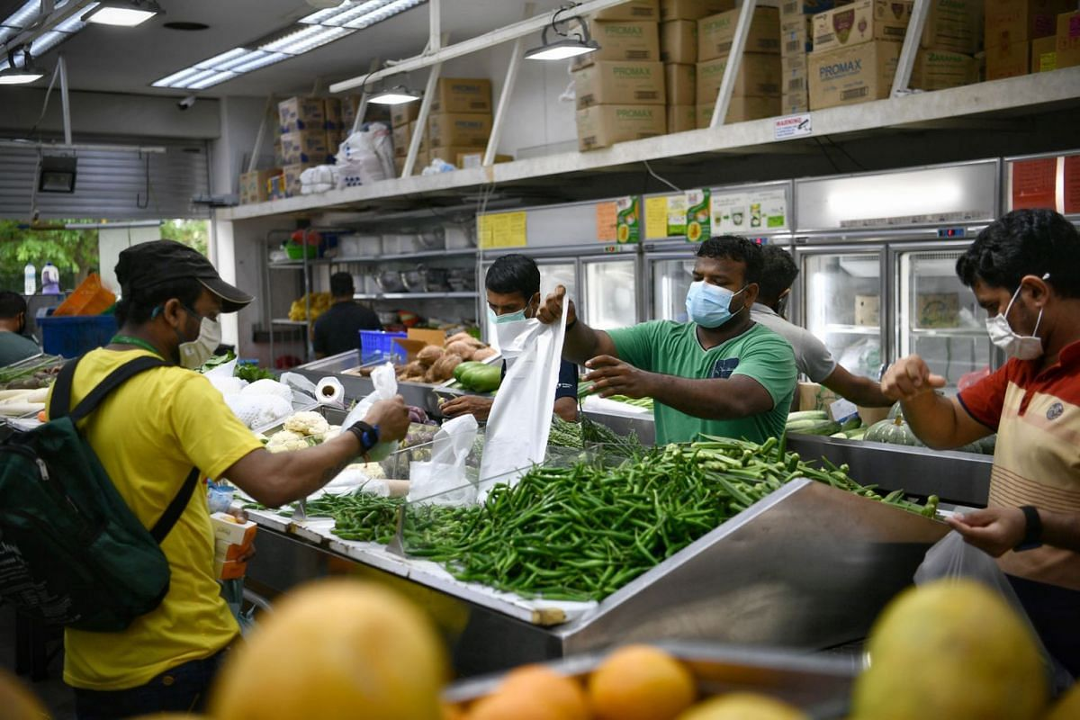 Foreign workers buying vegetables at the supermarket at Tuas South Recreation Centre.