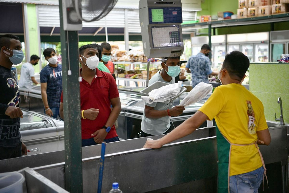 Foreign workers buying frozen foods at the supermarket at Tuas South Recreation Centre.