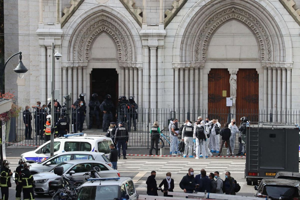 French members of the elite tactical police unit RAID enter to search the Basilica of Notre-Dame de Nice as forensics officers wait after a knife attack in Nice on October 29, 2020. A man killed three people at a basilica in central Nice and wounded