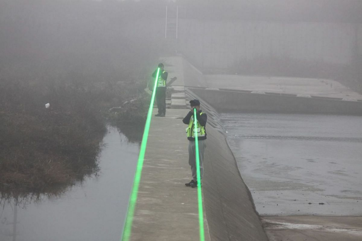 A handout photo made available by the Cheonan city government shows farmers shooting laser beams at migrant birds, believed to have been the source of a recent outbreak of avian influenza in the region, in Cheonan, some 160 kilometers south of Seoul,