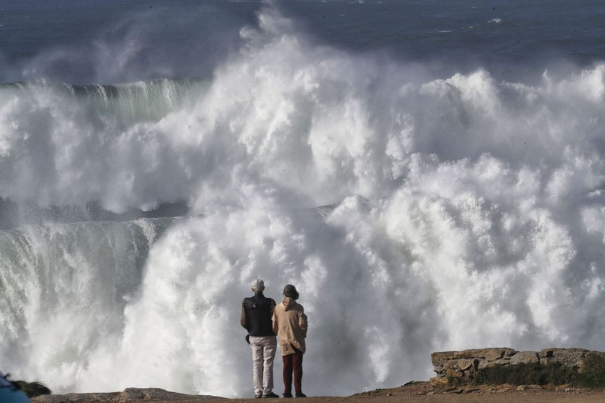 Tourists observe the big waves hitting the coast in Muxia, Galicia, northwest Spain, October 28, 2020, affected by the North Atlantic storm Epsilon.