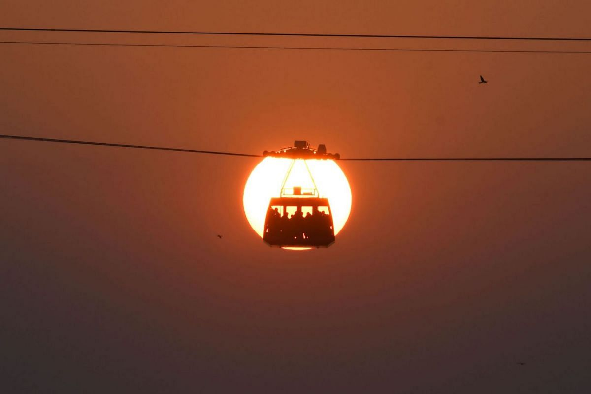 People travel in a cabin on India's longest river cable car connecting the northern and southern banks of the Brahmaputra river at sunset, in Guwahati on October 28, 2020.