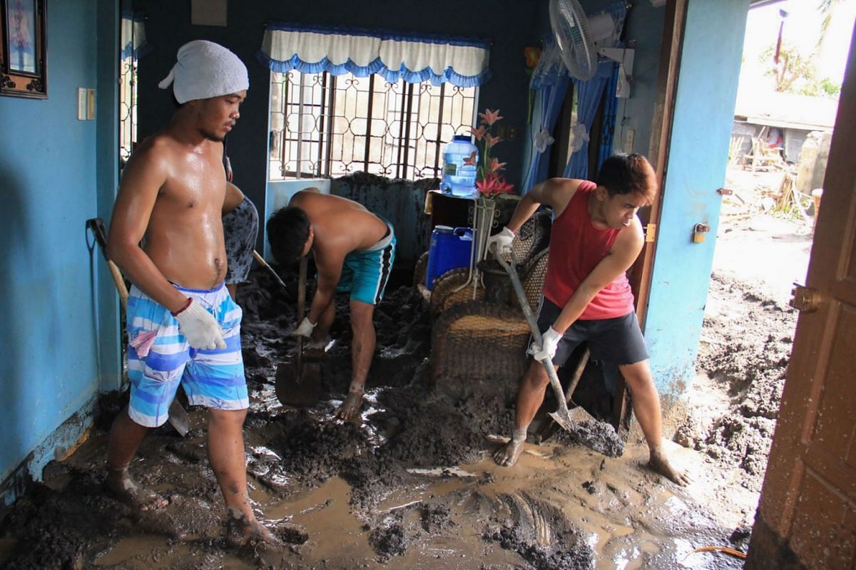 Residents clean their homes of volcanic ash mud washed from the slopes of nearby Mayon volcano in Guinobatan town, Albay province, on Nov 2, 2020.
