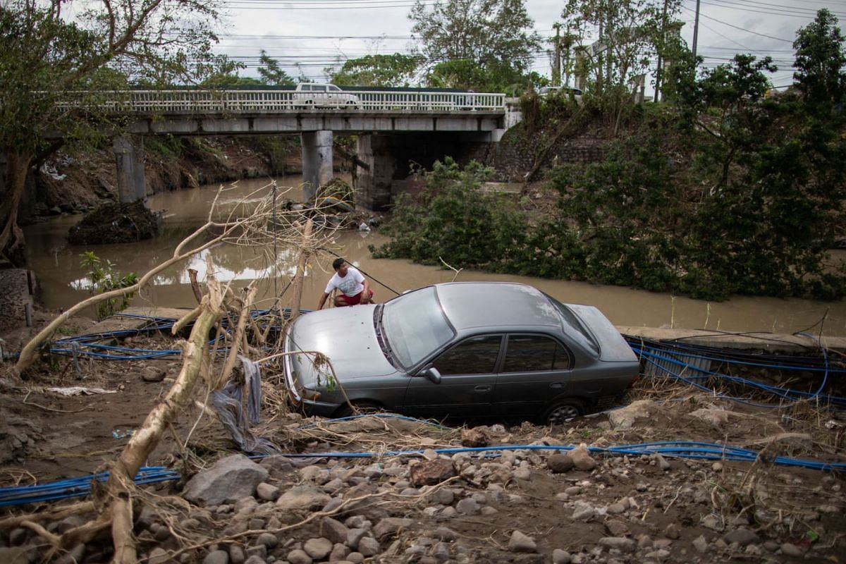 A man sits beside a car, washed away by floods caused by Typhoon Goni, in Barangay San Isidro, Batangas City, Philippines, Nov 2, 2020.
