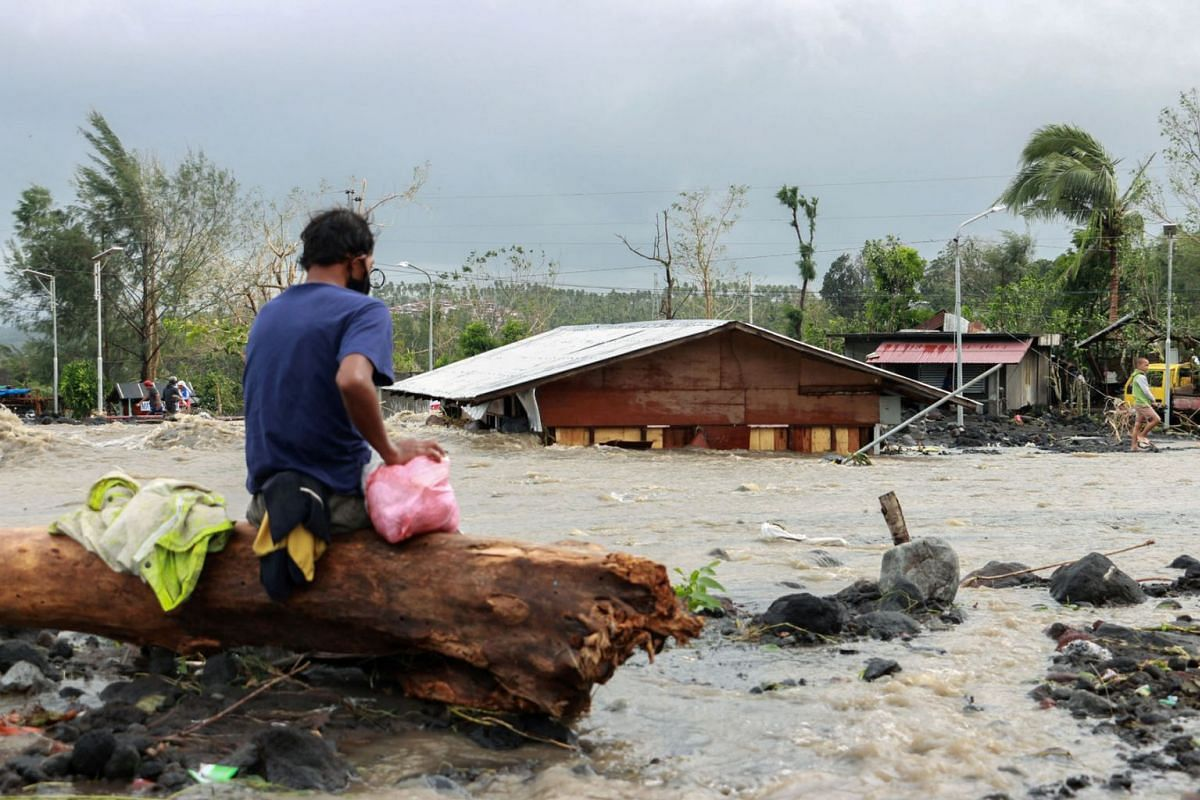 A man looks at his house buried under a pile of rubble and sand following flash floods brought on by Typhoon Goni in Barangay Busay, Daraga town, Albay province.