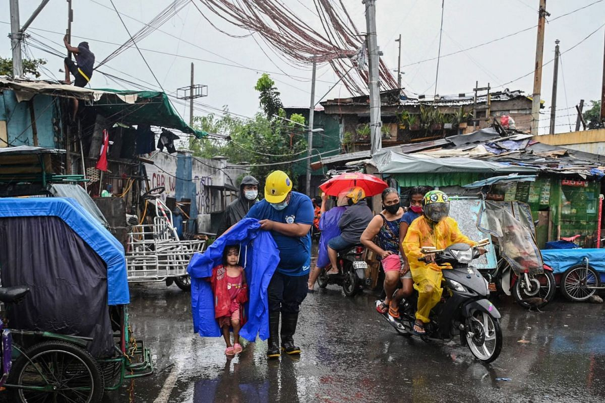 A rescue worker escorts a child to a waiting vehicle during an evacuation of informal settlers living along coastal areas in Manila on Nov 1, 2020, as Super Typhoon Goni moved towards the Philippine capital.