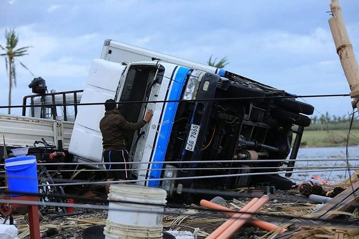 A resident inspecting a truck overturned at the height of Super Typhoon Goni after it hit Tabaco, Albay province on Nov 1, 2020.