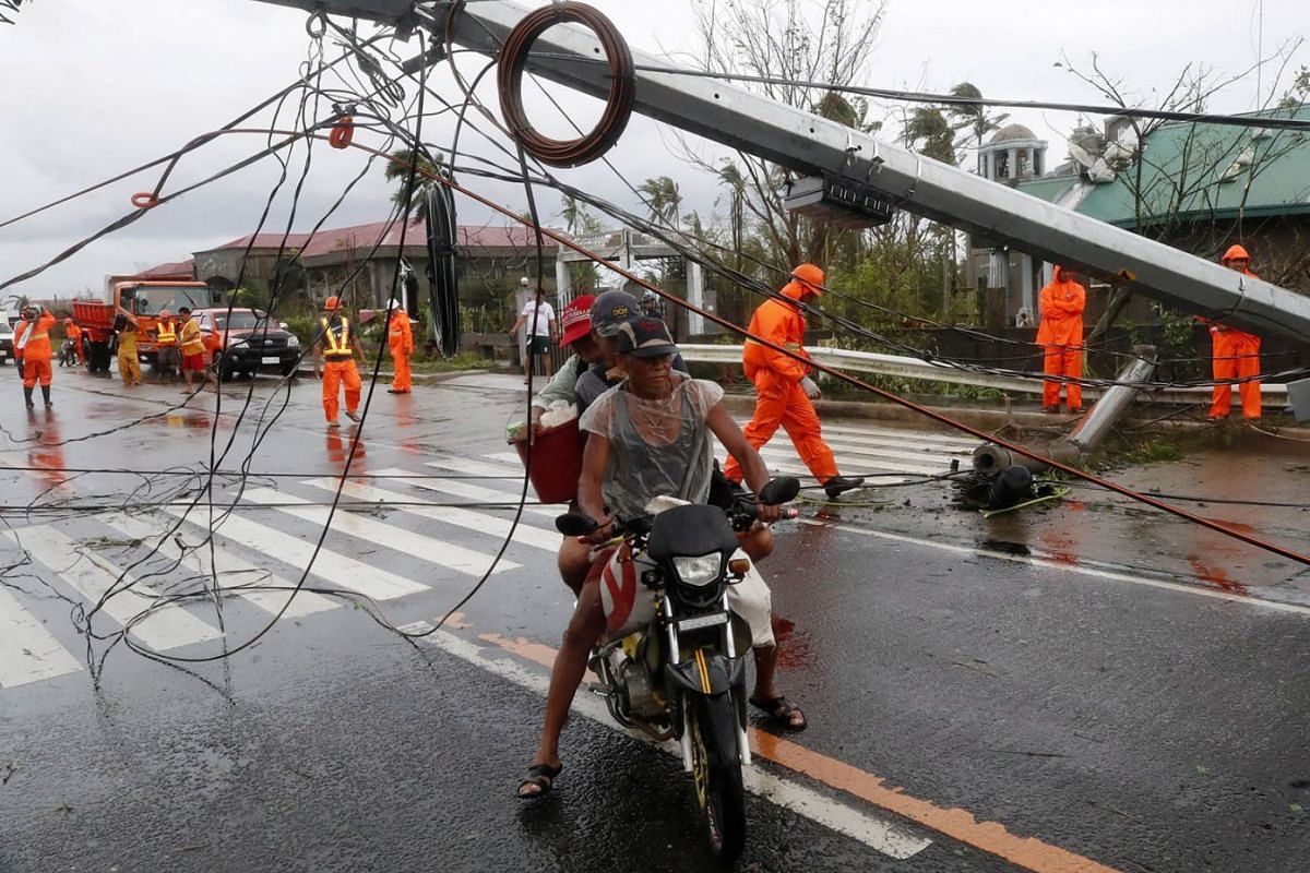 A bike rider manoeuvring under a toppled electric post in the typhoon-hit town of Tigaon, Camarines Sur, Nov 1,  2020.